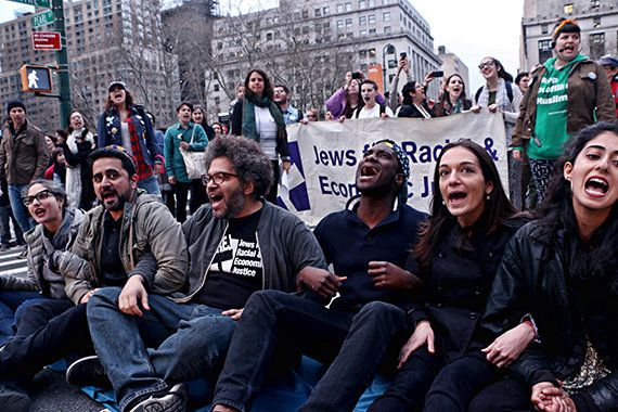 Six protestors from the JFREJ group (seated) were arrested Thursday after participating in a rally.