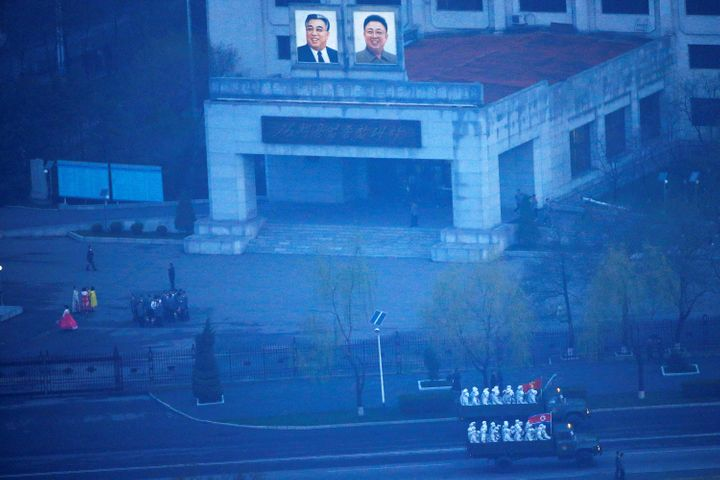 Military trucks carry soldiers through central Pyongyang before sunset as the capital preparers for a parade marking today's