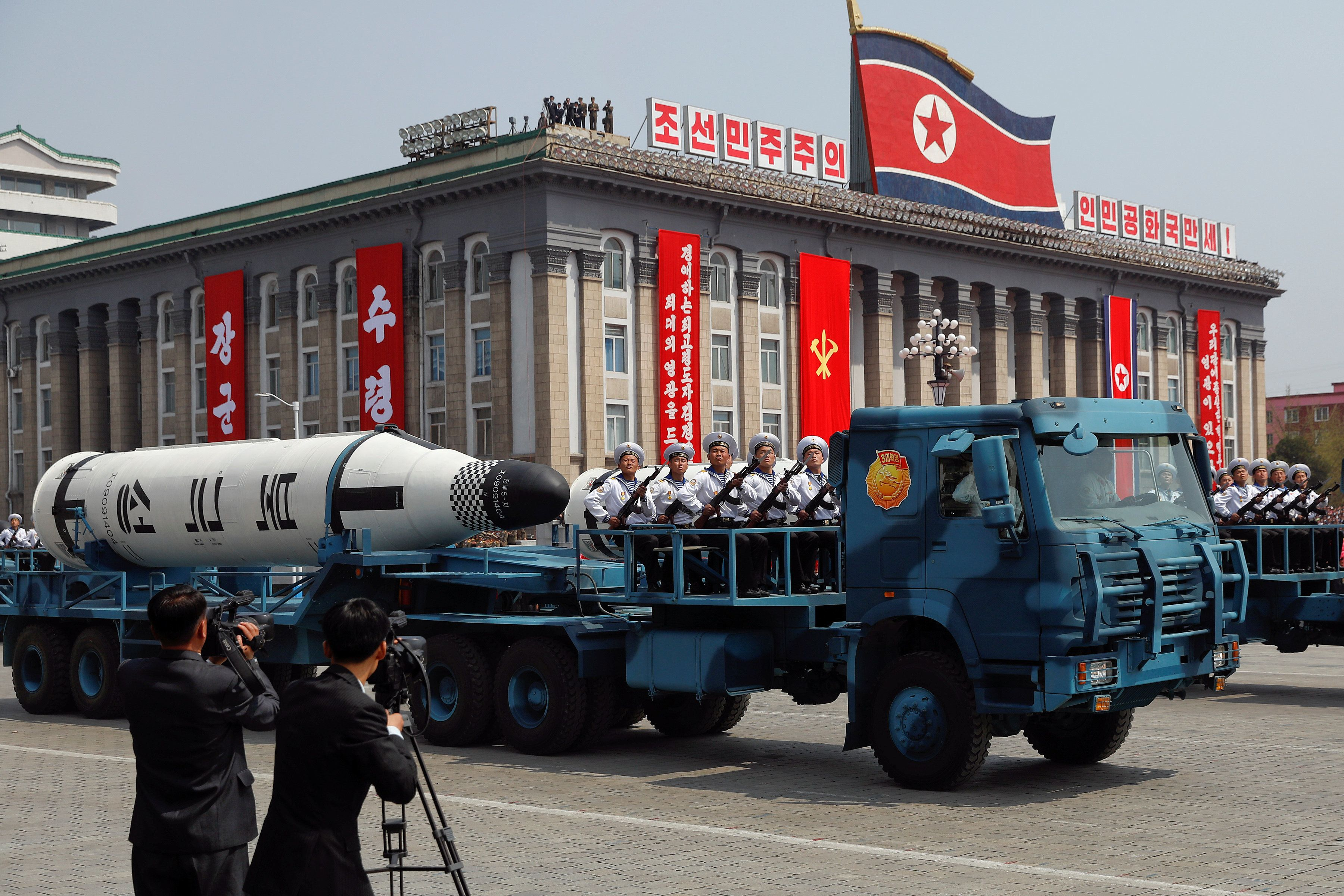 Military vehicles carry missiles with characters reading 'Pukkuksong' during a military parade marking the 105th birth annive