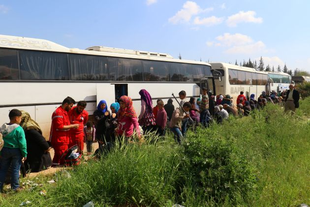 People who were evacuated from the two villages of Kefraya and al-Foua walk near buses, after a stall...