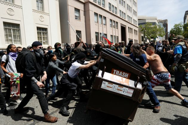 Demonstrators for (R) and against (L) U.S. President Donald Trump push a garbage container toward each...