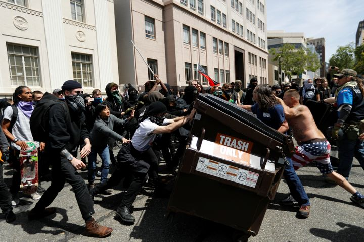 Demonstrators for (R) and against (L) U.S. President Donald Trump push a garbage container toward each other during a rally i