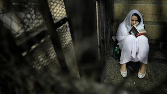 Aya Hijazi, founder of Belady, an NGO that promotes a better life for street children, sits reading a book inside a holding cell as she faces trial on charges of human trafficking at a courthouse in Cairo, Egypt March 23, 2017. Picture taken March 23, 2017. REUTERS/Mohamed Abd El Ghany     TPX IMAGES OF THE DAY