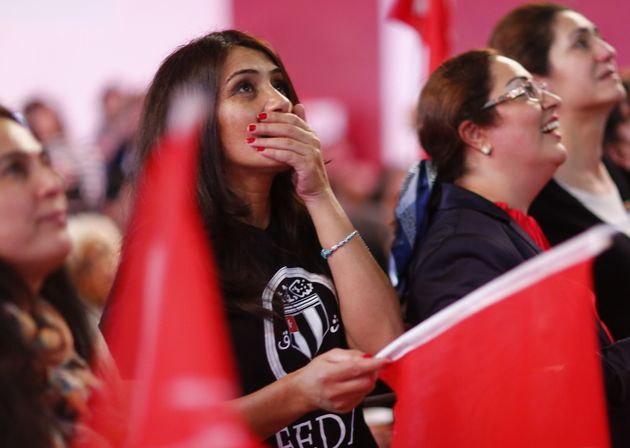 People of the Turkish community living in Germany react after first news bulletins on the outcome of...