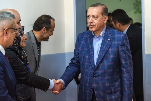 Turkish President Recep Tayyip Erdogan salutes official as he arrives at a polling station to vote in...