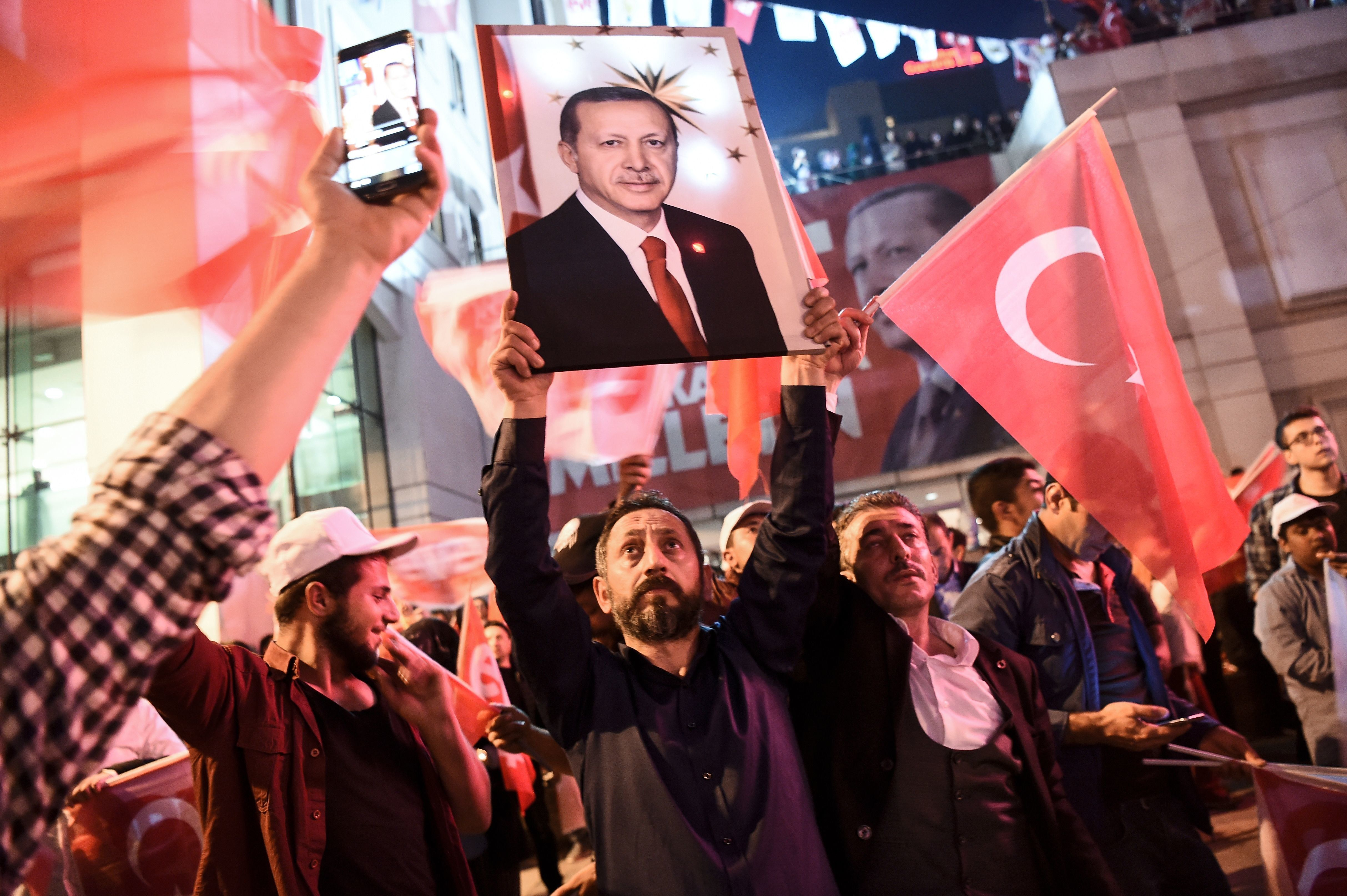 A supporter of the 'yes' brandishes a picture of Turkish president Recep Tayyip Erdogan among other supporters...