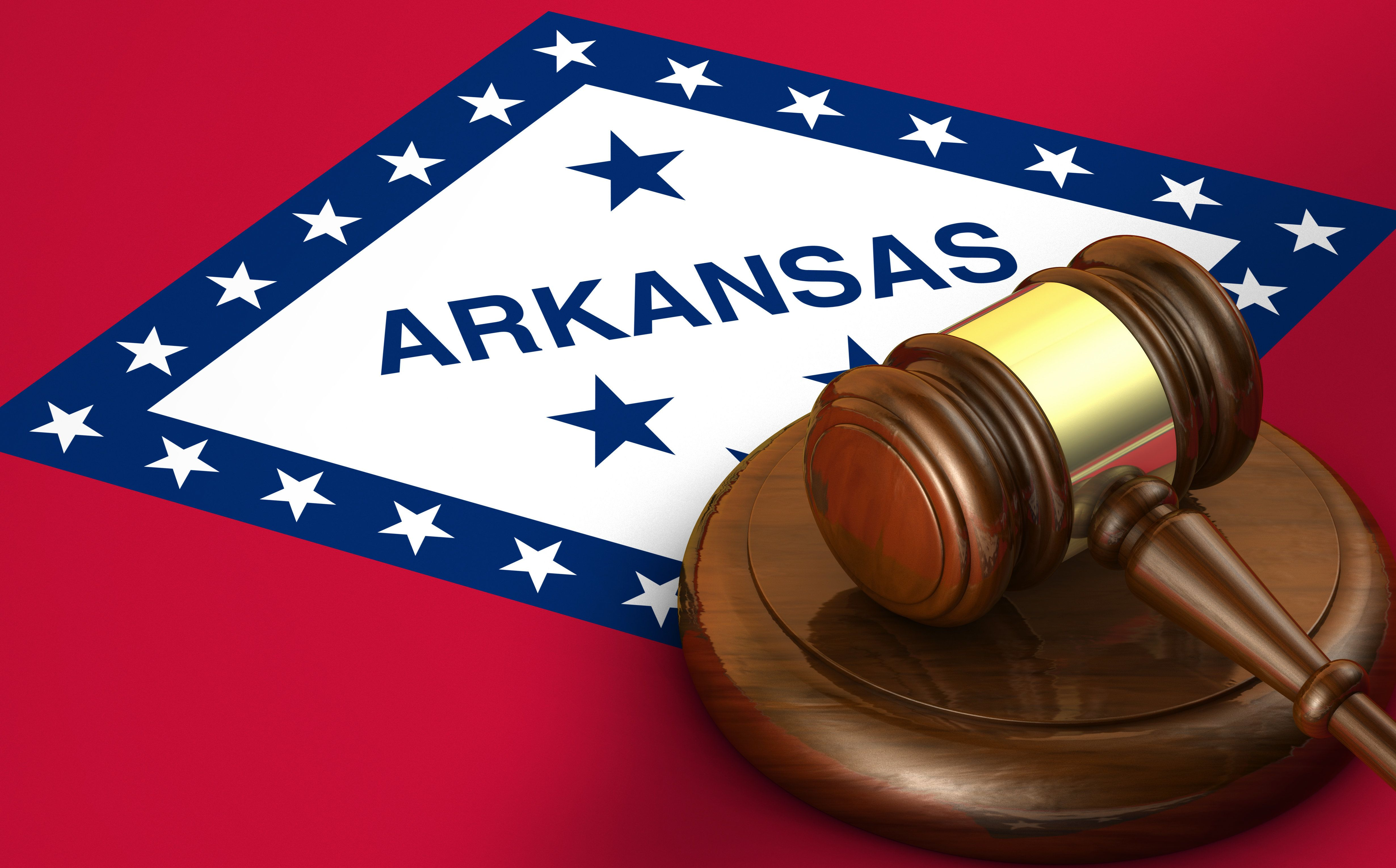 Arkansas US state law, code, legal system and justice concept with a 3d render of a gavel on the Arkansan flag on background.