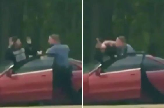 Demetrius Hollins is seen being punched in the head just after he exits his vehicle with his arms raised.
