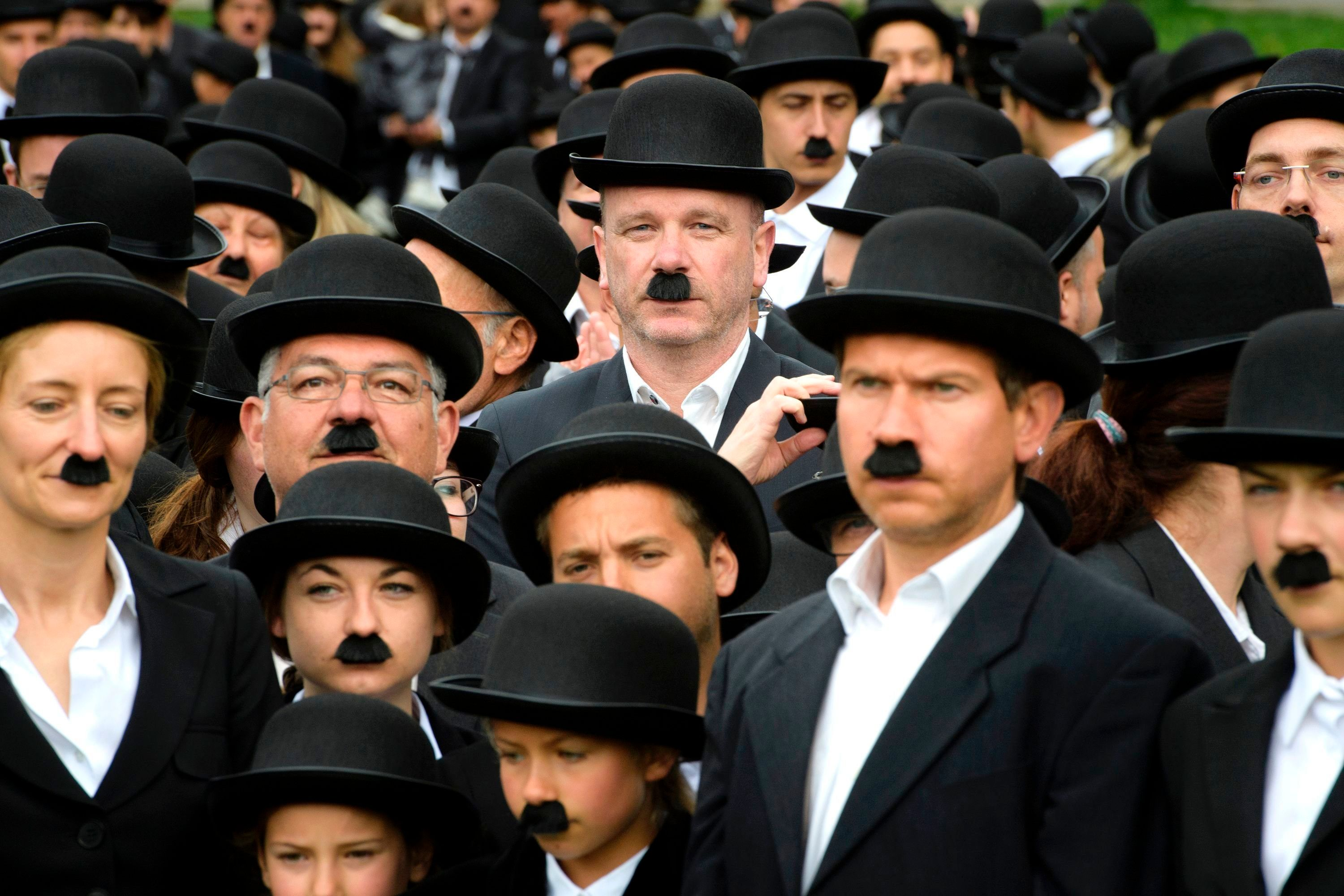 Some 662 people dressed as 'The Tramp' pose for a group picture to mark the first anniversary of Chaplins World By Grevin, and Charlie Chaplins birthday, as the museum plans to set the record for the worlds largest gathering of people dressed as The Tramp, on April 16, 2017 in Corsier-sur-Vevey.  Chaplins World, a large-scale museum dedicated to Charlie Chaplin and his lifes work is located in the Manoir de Ban and its park where Chaplin and his family lived through 1952 -1977.  / AFP PHOTO / Richard Juilliart        (Photo credit should read RICHARD JUILLIART/AFP/Getty Images)