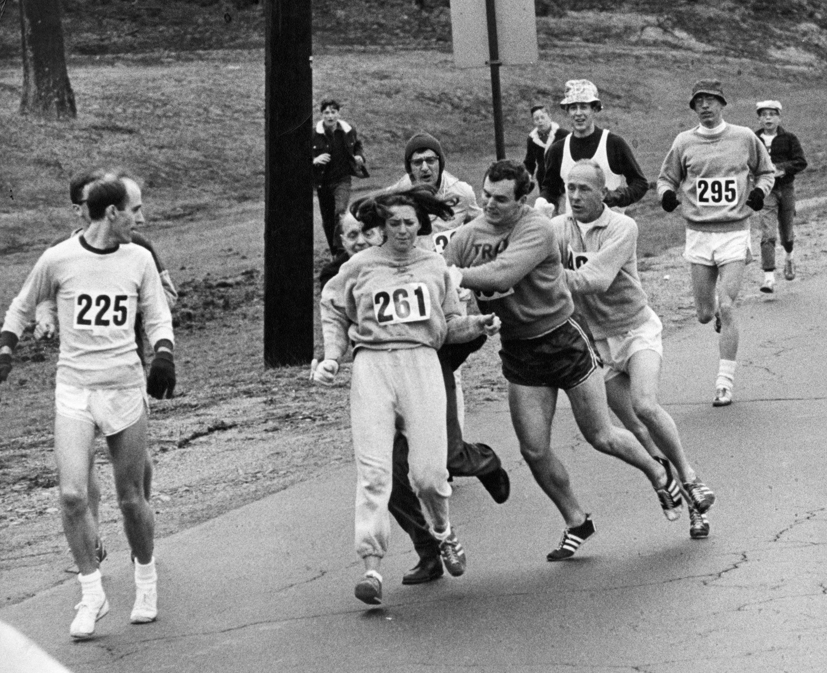 BOSTON, MA - APRIL 19: Kathrine Switzer, of Syracuse, N.Y., center, was spotted early in the Boston Marathon by Jock Semple, center right, who tried to rip the number off her shirt and remove her from the race. Switzer's friends intervened, allowing her to make her getaway to become the first woman to 'officially' run the Boston Marathon on April 19, 1967. (Paul Connell/The Boston Globe via Getty Images)