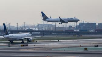 A United Continental Holdings Inc. airplane prepares for landing at Newark Liberty International Airport (EWR) in Newark, New Jersey, U.S., on Wednesday, April  12, 2017. United Airlines is under fire for forcibly removing a passenger from a plane in Chicago shortly before departure to make room for company employees, an incident which demonstrates how airline bumping can quickly veer into confrontation. Photographer: Timothy Fadek/Bloomberg via Getty Images