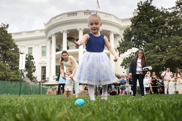 Four-year-old Vittoria Colonna of Marcus Hook, Pennsylvania, rolls a colored egg down the White House South Lawn.
