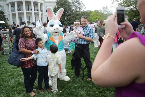 Families pose for photographs with one of the costumed Easter Bunny characters.