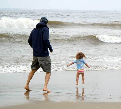 Chris Williams and his daughter play together down by the edge of the Pacific Ocean