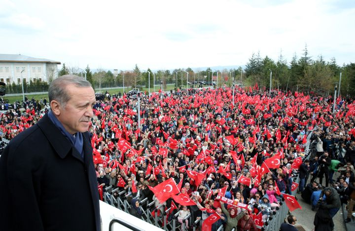Erdogan greets the crowd, who were waiting to celebrate the results of the referendum, after he arrived in the Esenboga Inter