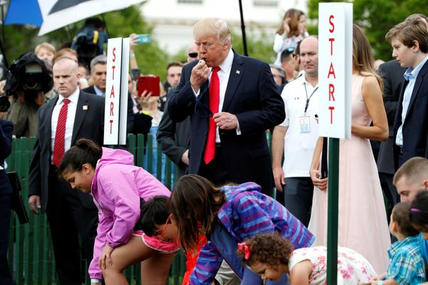 Trump blows a whistle to start the White House Easter Egg Roll alongside his wife, Melania, and his youngest son, Barron.