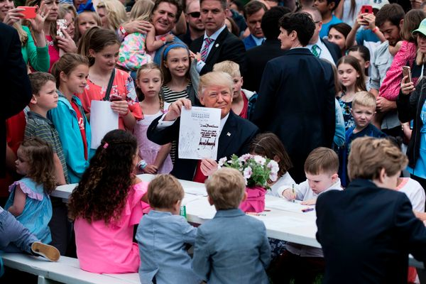 Trump shows a note he wrote while writing notes to service members with children.