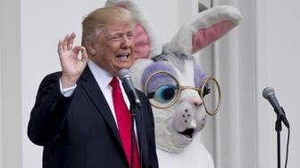 US President Donald Trump speaks alongside the Easter Bunny during the 139th White House Easter Egg Roll on the South Lawn of the White House in Washington, DC, April 17, 2017. / AFP PHOTO / SAUL LOEB        (Photo credit should read SAUL LOEB/AFP/Getty Images)