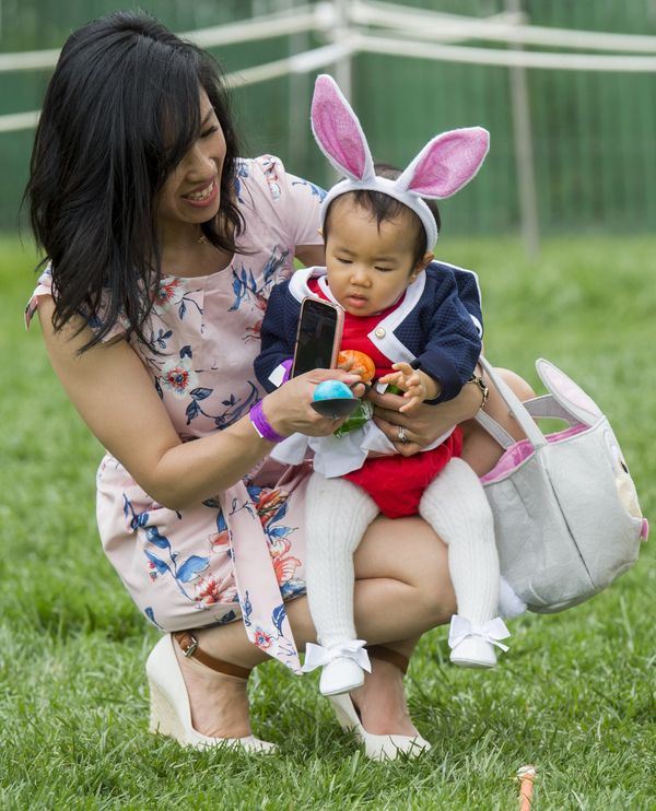 Cynthia Cheng of San Francisco helps her daughter, 11-month-old Victoria, participate in an Easter egg roll race.