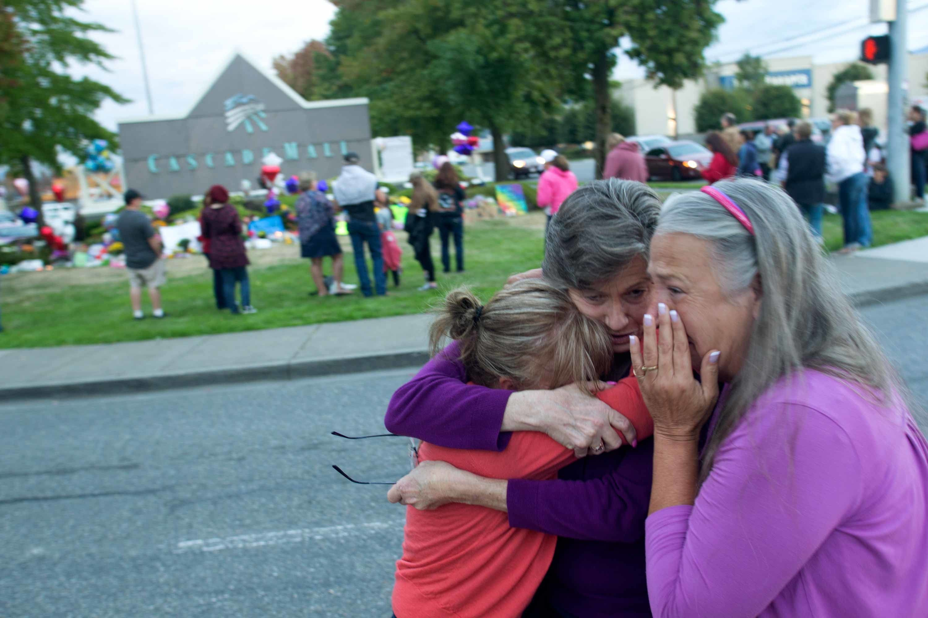 BURLINGTON, WA - SEPTEMBER 26: (L-R) Darci Ridenhour, Kathy Shelman, and Patti Bannister weep after leaving flowers at a memorial outside the Cascade Mall on September 26, 2016 in Burlington, Washington. A candlelight vigil was held outside the Macy's department store where five people who  were shot and killed by a gunman on September 24. The suspect, Arcan Cetin of Oak Harbor, Washington, made a court appearance today. (Photo by Karen Ducey/Getty Images)