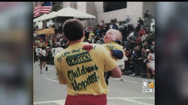 WBZ-TV Dave Prario carries his son Austin across the Boston Marathon finish line in 1998