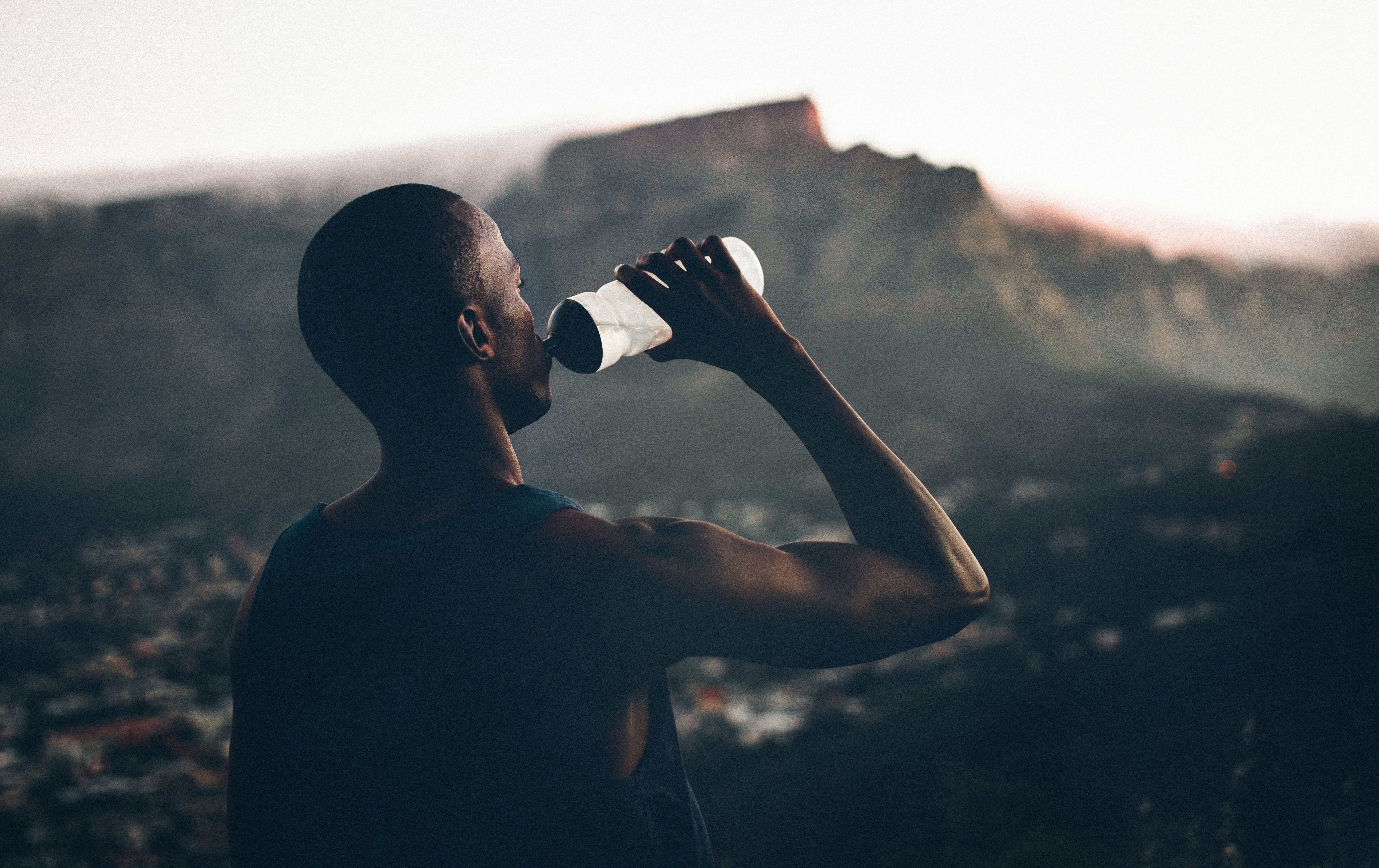 healthy fit african decent athlete drinking water after a fitness achievement with a great view of the mountain in the background in the late afternoon