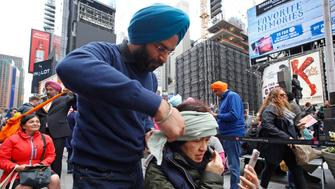 MANHATTAN, NEW YORK CITY, NY, UNITED STATES - 2017/04/15: Sikhs of New York arranged for Turban Day in Times Square. Volunteers were on hand to help tie traditional Sikh turbans for all comers, some followers of the religion, others not. Turban day is designed to educate people about Sikhism, a centuries old religion with origins in Northern India, & takes place as part of the April celebration of Vaisakhi. (Photo by Andy Katz/Pacific Press/LightRocket via Getty Images)