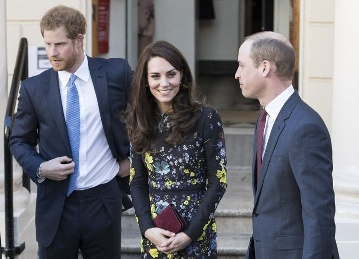 <p>Prince Harry and the Duchess & Duke of Cambridge in London earlier this year. Harry is wearing a suit with a blue tie, the Duchess is wearing a black dress with grey and yellow flowers, and the Duke is wearing a suit with a maroon tie.</p>