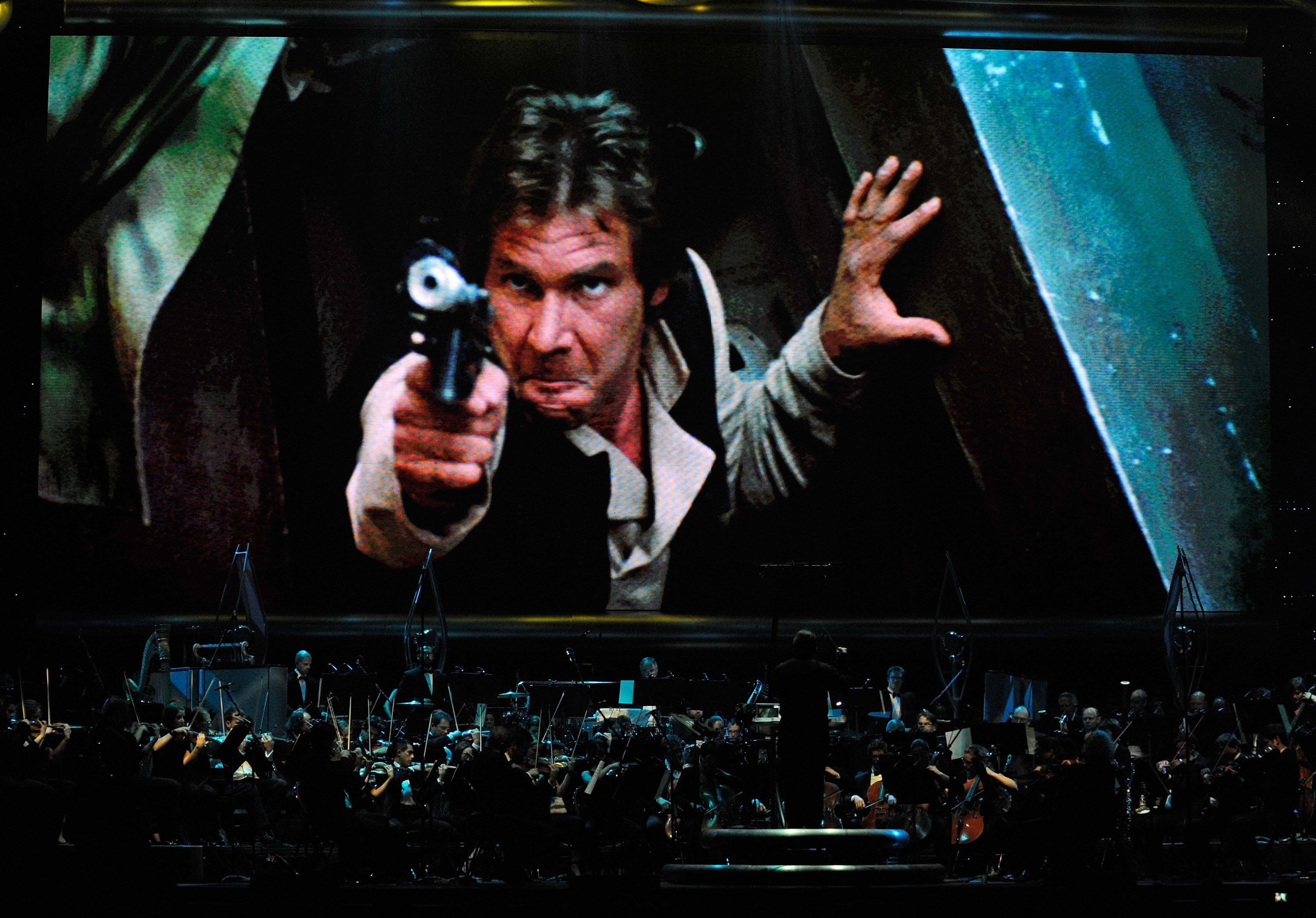LAS VEGAS - MAY 29:  Actor Harrison Ford's Han Solo character from 'Star Wars Episode VI: Return of the Jedi' is shown on screen while musicians perform during 'Star Wars: In Concert' at the Orleans Arena May 29, 2010 in Las Vegas, Nevada. The traveling production features a full symphony orchestra and choir playing music from all six of John Williams' Star Wars scores synchronized with footage from the films displayed on a three-story-tall, HD LED screen.  (Photo by Ethan Miller/Getty Images)