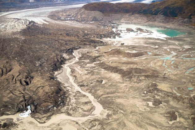 Photo shows the meltwater stream along the toe of Kaskawulsh Glacier seen on the left that is diverting...