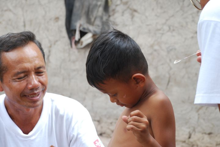 A young boy in Cambodia is screened for leprosy symptoms with the use of a feather.