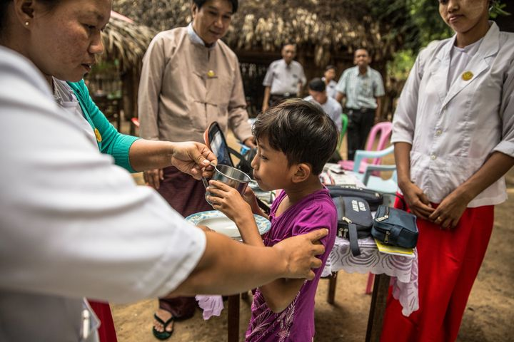 A child in Myanmar drinks water to help her swallow her dose of the  post-exposure prophylaxis, Rifampicin.