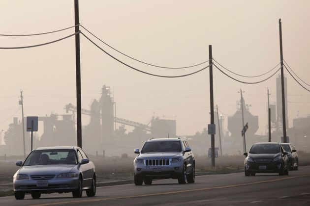 Vehicles travel on a road in Bakersfield, California during a day of poor air quality in 2014. Bakersfield...