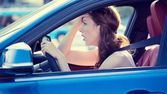 Side view window portrait displeased stressed angry pissed off woman driving car annoyed by heavy traffic isolated street background. Emotional intelligence concept. Negative human face expression