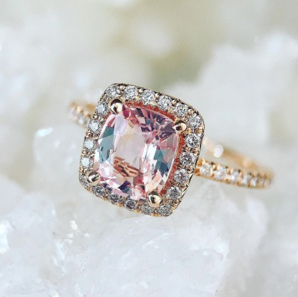 """<i>Buy it at <a href=""""https://trabertgoldsmiths.com/products/1-26ct-cushion-peach-sapphire-goddess-halo-ring"""" target=""""_blank"""""""