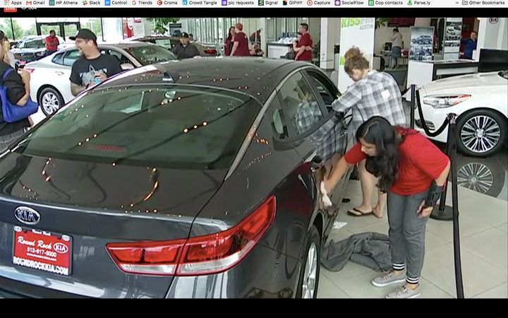 A contestant tries to wipe away smudges left by another contestant on the side of a car during a 10 minute break.