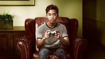 Asian man playing game on the living room