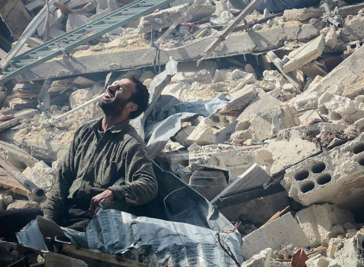 A Douma man waits for news of his wife and child buried beneath the ruins of their house. His wife survived while his child d