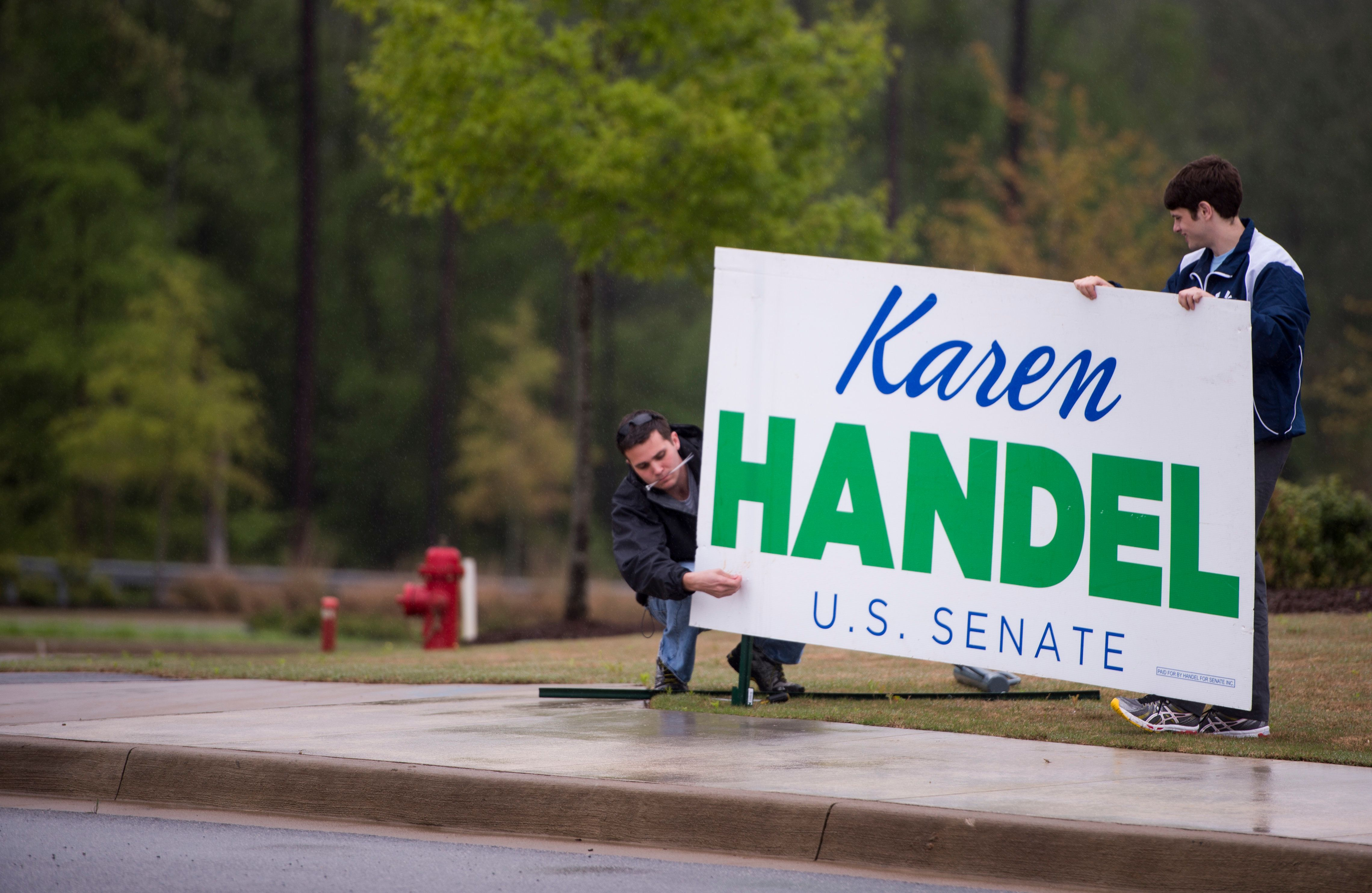 UNITED STATES - APRIL 19: Karen Handel campaign workers erect a campaign sign before the debate of Republican candidates vying for Georgia's open U.S. Senate seat at the Columbia County Exhibition Center in Grovetown, Ga., outside of Augusta, on Saturday, April 19, 2014.  (Photo By Bill Clark/CQ Roll Call)