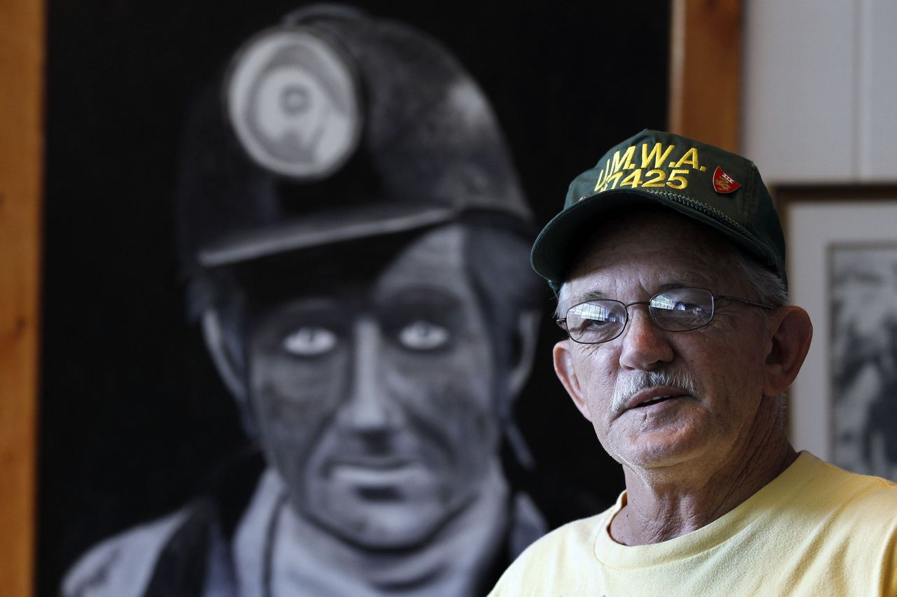 Carl Shoupe stands by a painting of a coal miner in the Kentucky Coal Mining Museum in Benham, Kentucky, in 2011.