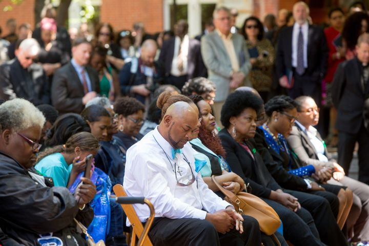An audience participates in a moment of silence in front of Isaac Hawkins hall during a dedication of it and neighboring Anne
