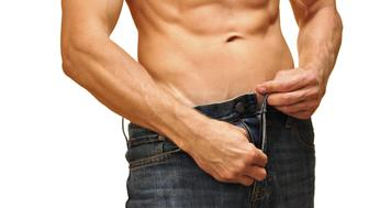 Sexy man with lean abdominals unzips his jeans on white background