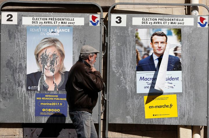 Official campaign posters showing Le Pen and Emmanuel Macron in Paris.