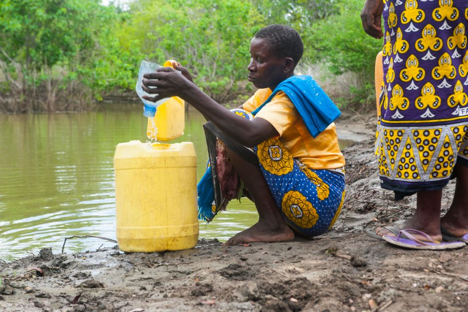Kanze Kahindi, 40, fills a jerrycan with about 5 gallons of water. Her walk home, with the container...