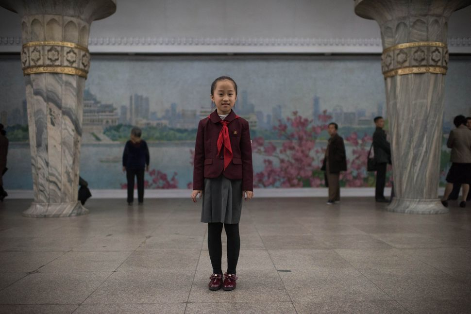 Student Jo Chong-A, 10, poses for a portrait in a subway station of the Pyongyang metro.
