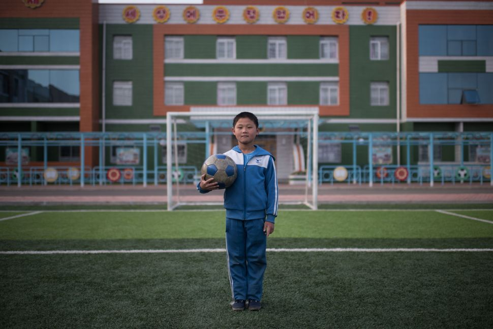 Jong Kwang-Hyok, 10, poses for a portrait on a football field at a school for orphans on the outskirts of Pyongyang.
