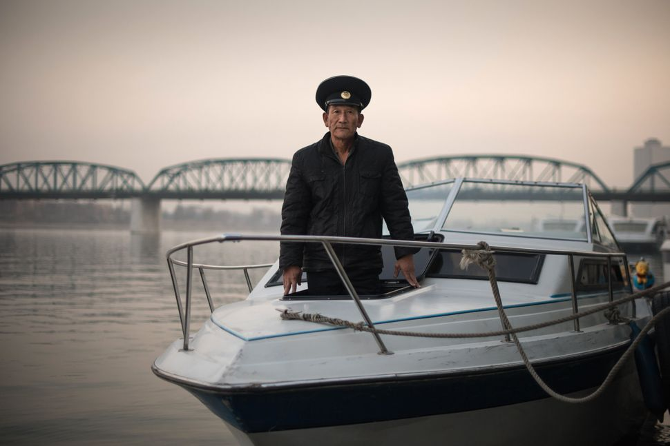 Sailor Kim Il-Su poses for a photo on a boat used to host wedding photo shoots on the Taedong river in Pyongyang.