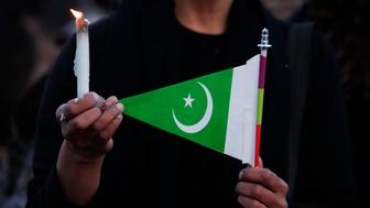 A woman holds a candle and a Pakistani flag as she takes part in a protest against terrorism in Islamabad March 17, 2015. Suicide bombings outside two churches in Lahore killed 14 people and wounded nearly 80 others during services on Sunday in attacks claimed by a faction of the Pakistani Taliban.  REUTERS/Faisal Mahmood (PAKISTAN - Tags: POLITICS CIVIL UNREST)