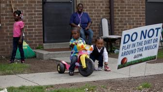 EAST CHICAGO, IN - SEPTEMBER 4: Nayesa Walker (center top) watches as her son KaJuan Lott (on tricycle) and Logan Anderson, right, play as Kaelynn Lott, left, walks away at the West Calumet Housing Complex on September 4, 2016 in East Chicago, Indiana. The soil at the complex has been found to contain high levels of lead and arsenic putting all residents in danger if exposed to the elements. Over 1,000 residents are being asked by the East Chicago Housing Authority to relocate, after plans were decided to demolish the housing complex. (Photo by Joshua Lott/Getty Images)