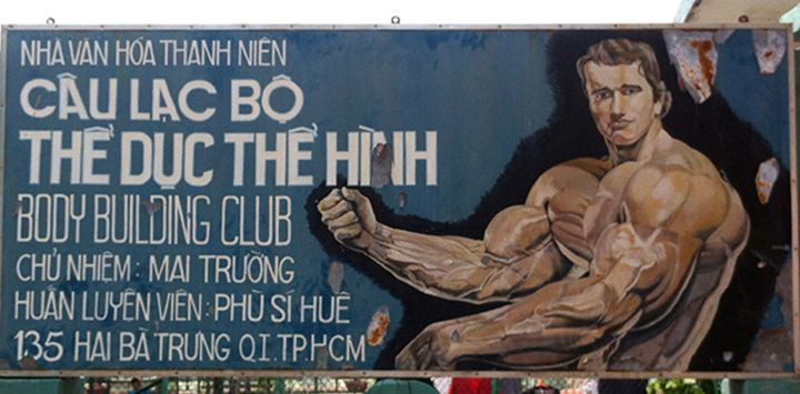 A hand-painted folk portrait of Arnold Schwarzenegger advertising a Ho Chi Minh City bodybuilding gym, photographed in 2011.